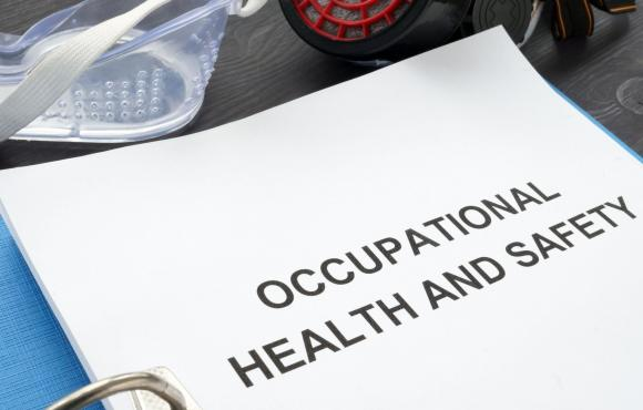 "An image of a binder on a table open to a title page that says ""Occupational Health and Safety"" with safety goggles on the table next to it"