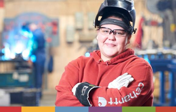 A young First Nations woman is standing with her arms crossed, smiling while standing in the welding bay. She is wearing a welding shield on top of her head and there is a blurred out person welding with sparks flying in the background.