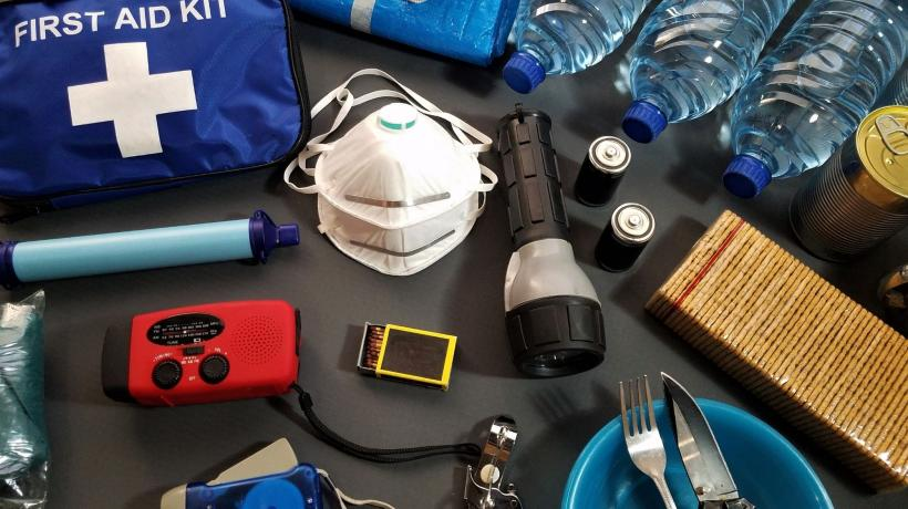 emergency items such as a mask, first aid kit, water bottles, matches, and more are splayed out on a table