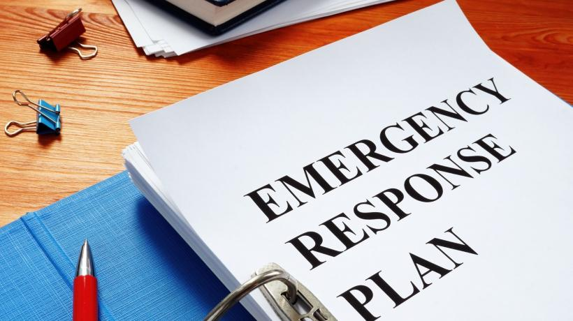"a binder is open to a title page with the words ""Emergency response plan"" written on a blank white page"