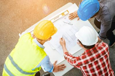 An aerial shot of three people standing around a set of engineering plans wearing hard hats